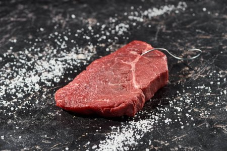 Photo for Raw meat steak with metal hook on black marble surface with scattered salt - Royalty Free Image
