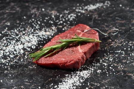 Photo pour Steak de viande crue avec brindille de romarin sur la surface de marbre noir avec sel dispersé - image libre de droit