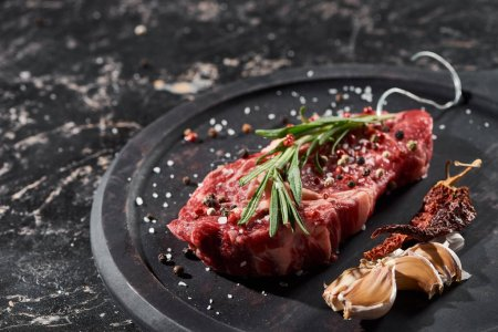 Photo for Raw meat steak with rosemary twig sprinkled with salt and pepper near garlic and dried cayenne on round wooden surface - Royalty Free Image
