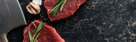 Photo for Panoramic shot of unprocessed beef steaks with rosemary sprigs near garlic and knife on black marble surface - Royalty Free Image