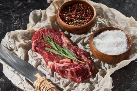 Photo for Raw beef steak near knife and wooden bowls with salt and pepper on black marble surface - Royalty Free Image