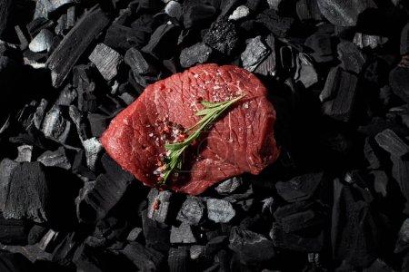 Photo pour Vue du dessus du bifteck cru de boeuf avec le romarin, le sel et le poivre sur des charbons de bois - image libre de droit
