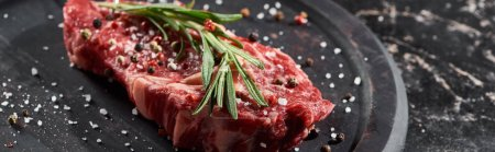 Photo for Panoramic shot of raw beef fillet with rosemary twig sprinkled with salt and pepper on round wooden surface - Royalty Free Image