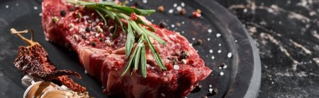 Photo for Panoramic shot of raw beef fillet with rosemary twig sprinkled with salt and pepper near garlic and cayenne on round wooden surface - Royalty Free Image