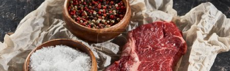 Photo for Panoramic shot of raw beef fillet near wooden bowls with salt and peppercorns on parchment paper - Royalty Free Image
