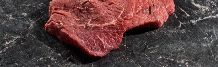 Photo for Panoramic shot of fresh uncooked beef sirloin on black marble surface - Royalty Free Image