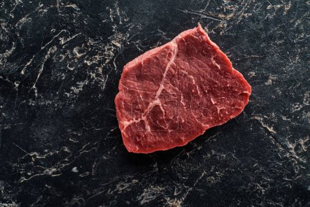 top view of uncooked beef sirloin on black marble background