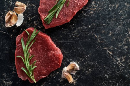 Photo for Top view of uncooked beef sirloins with garlic and rosemary on black marble background - Royalty Free Image