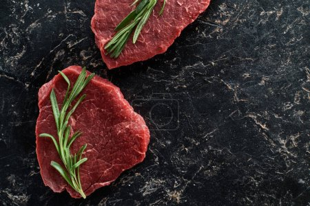 Photo for Top view of uncooked beef sirloins with rosemary on black marble background - Royalty Free Image