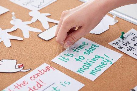 Photo pour Vue recadrée de la carte d'épinglage de femme avec des notes de travail sur le panneau de liège - image libre de droit