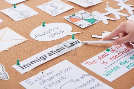 Photo pour Vue recadrée de femme pointant avec le crayon sur l'inscription de loi d'immigration sur le panneau de liège - image libre de droit