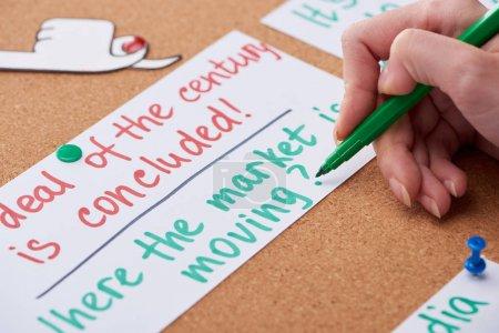 Photo pour Vue recadrée de femme écrivant des notes de travail sur la carte épinglée sur le panneau de liège - image libre de droit