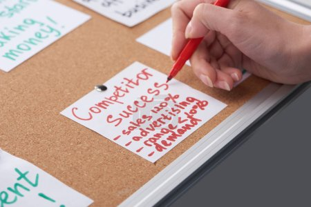 Photo for Cropped view of woman writing competitor success notes on card pinned on cork board - Royalty Free Image