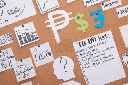 Photo for Top view of cards with income plan notes pinned on office cork board - Royalty Free Image