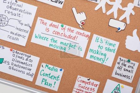 Photo pour Vue du haut des cartes avec des notes de travail et des tâches épinglées sur le panneau de liège de bureau - image libre de droit