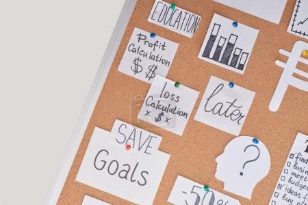 Photo pour Vue du haut des cartes avec des notes financières et des graphiques épinglés sur le panneau de liège de bureau - image libre de droit