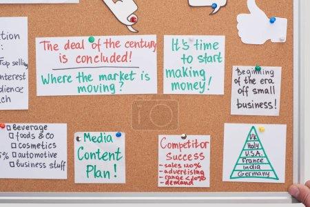 Photo pour Vue du haut des cartes avec des notes de plan de travail épinglées sur le panneau de liège de bureau - image libre de droit