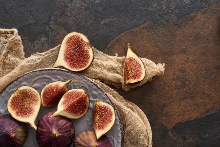 Photo for Top view of ripe figs on white plate with rustic cloth on stone background - Royalty Free Image