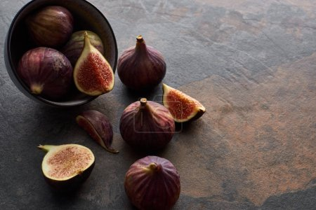 ripe whole and cut delicious figs scattered from bowl on stone background