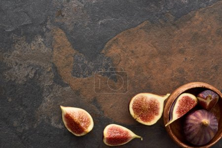 top view of ripe whole and cut delicious figs near wooden bowl on stone background