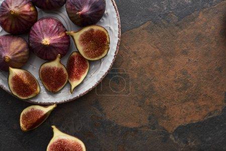 vue de dessus de figues entières mûres et coupées délicieuses sur plaque sur fond de pierre