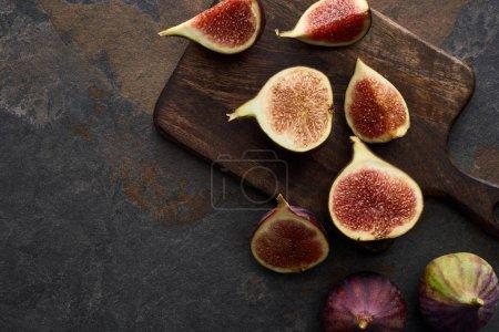 Photo pour Vue du dessus de figues fraîches et délicieuses mûres sur planche à découper sur fond de pierre - image libre de droit