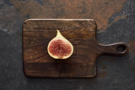 Photo for Top view of ripe cut delicious fig on wooden cutting board on stone background - Royalty Free Image