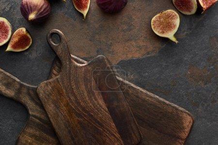 Photo pour Vue supérieure des figues savoureuses et des planches à découper en bois sur le fond en pierre - image libre de droit