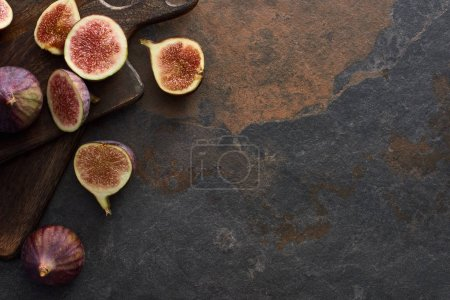 top view of ripe delicious figs and wooden brown cutting boards on stone background