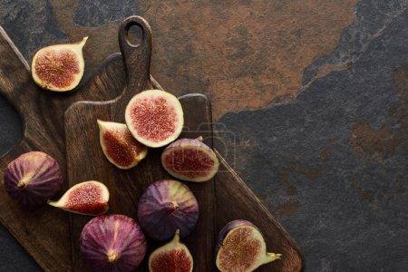 top view of ripe whole and cut delicious figs and cutting boards on stone background