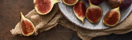 Photo for Panoramic shot of cut ripe figs on white plate with rustic cloth on stone background - Royalty Free Image