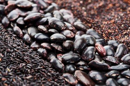 Nahaufnahme schwarzer Bohnen zwischen Quinoa und Reis