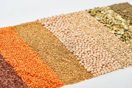 Photo for Uncooked red lentil, buckwheat, chickpea, maash and pumpkin seeds isolated on white - Royalty Free Image