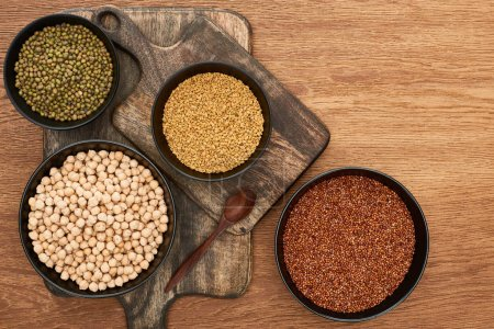 Photo for Top view of bowls with moong beans, buckwheat and chickpea near spoon on wooden cutting boards - Royalty Free Image