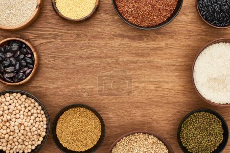 Photo for Top view of bowls with beans, white rice, couscous and buckwheat and chickpea on wooden surface - Royalty Free Image