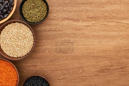 Photo for Top view of bowls with black and moong beans, buckwheat and red lentil on wooden surface - Royalty Free Image