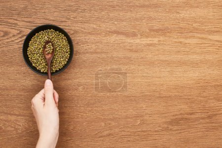 cropped view of woman holding picking with spoon raw moong beans from bowl on wooden surface
