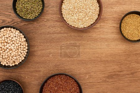 Photo for Top view of bowls with beans, buckwheat and chickpea on wooden surface with copy space - Royalty Free Image