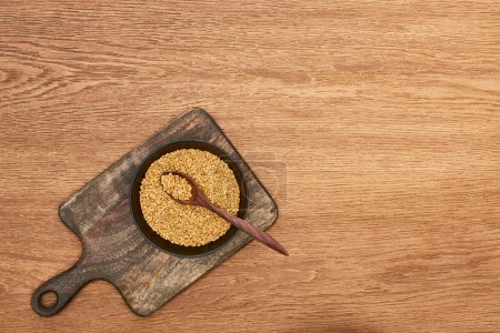 Photo for Top view of bowls whole grains with spoon on wooden cutting board - Royalty Free Image