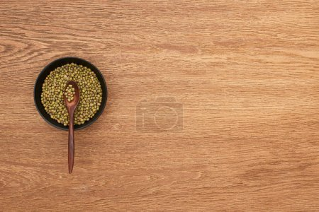 Photo for Top view of bowl with moong beans with spoon on wooden surface - Royalty Free Image