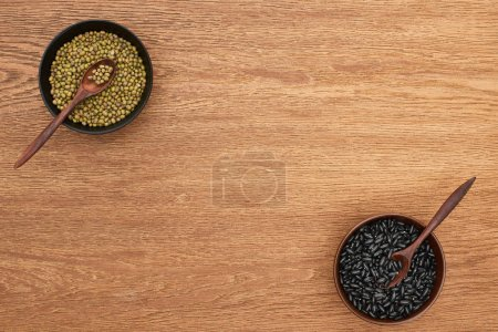 Photo for Top view of bowls with moong and black beans with spoons on wooden surface - Royalty Free Image