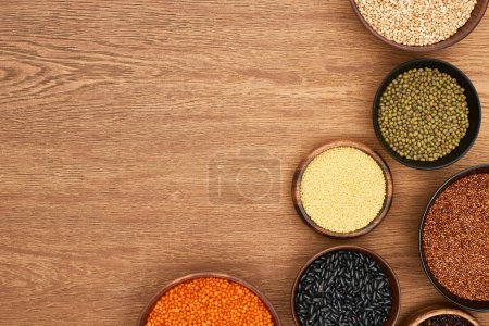 Photo for Top view of bowls with black beans, maash, red lentil, couscous and buckwheat on wooden surface - Royalty Free Image