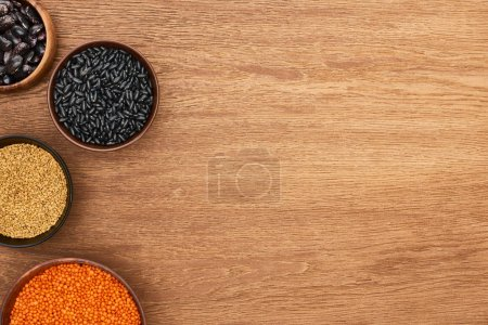 Photo for Top view of bowls with beans, red lentil, and cereal on wooden surface - Royalty Free Image