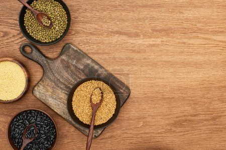 Photo for Top view of cutting board with bowls with black beans, maash, couscous and buckwheat on wooden surface - Royalty Free Image