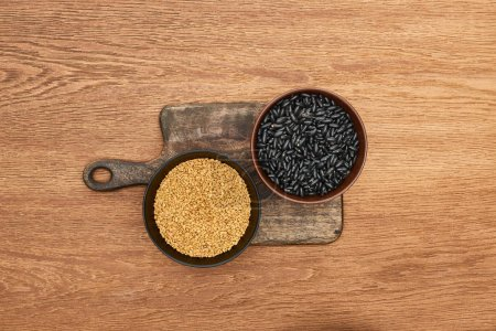Photo for Top view of bowls with beans and grains on wooden cutting board - Royalty Free Image