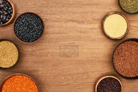 Photo for Top view of bowls with quinoa, couscous, beans, chickpea and lentil on wooden surface - Royalty Free Image