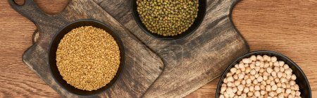 Photo for Panoramic shot of bowls with beans, grains and chickpea on wooden cutting boards - Royalty Free Image