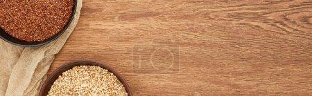 Foto de Foto panorámica de cuencos con diverso trigo sarraceno en superficie de madera con lienzo - Imagen libre de derechos