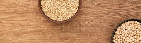 Photo for Bowls with raw buckwheat and chickpea on wooden surface with copy space - Royalty Free Image
