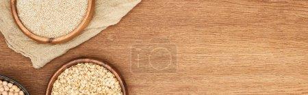 Foto de Foto panorámica de cuencos con avena, garbanzo y quinua blanca sobre superficie de madera con lona - Imagen libre de derechos